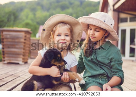 Two cute little sisters hugging dog puppy. Friendship and care concept - stock photo