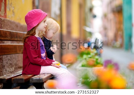 Two cute little sisters sitting on a bench outdoors on hot and sunny summer day - stock photo