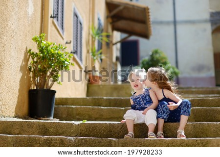 Two cute little sisters sitting on stairs in italian town - stock photo