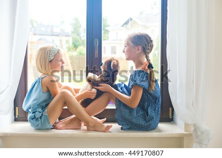 Two cute russian toddler girls sitting near window at home playing teddy bears happy and funny. Colorful back yard at background - stock photo