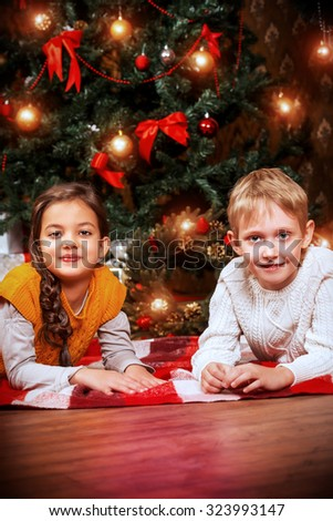 Two cute seven year old children with gifts by the Christmas tree at home. The magic of Christmas. - stock photo