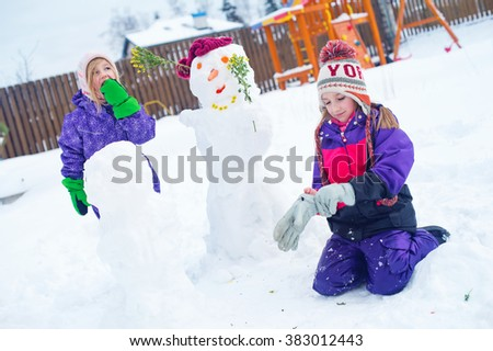 Two cute sister girls play in winter with snow man outside on backyard of village country house - stock photo