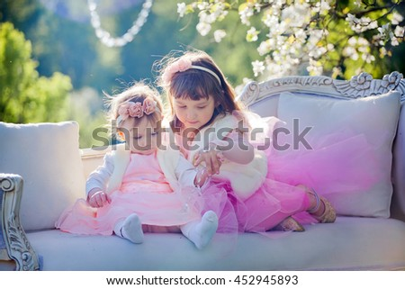 Two cute sisters in spring blossom garden - stock photo