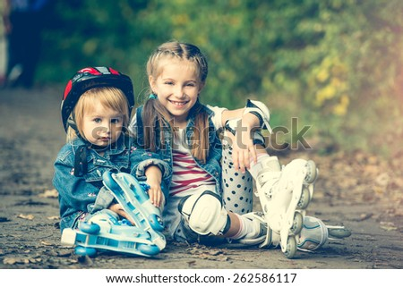two cute sisters on roller skates in park - stock photo
