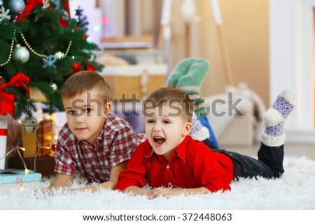 Two cute small brothers lie on carpet on Christmas tree background - stock photo