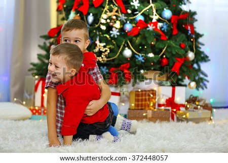 Two cute small brothers playing on Christmas tree background - stock photo