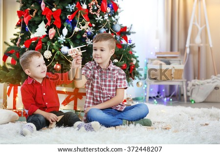 Two cute small brothers playing with wooden plane on Christmas tree background - stock photo