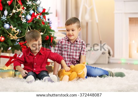 Two cute small brothers with teddy bear on Christmas tree background - stock photo