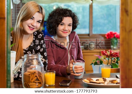 Two cute teen girl friends having tea and cookies together at home. - stock photo
