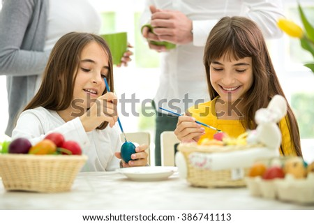 two cute twins girls painted Easter eggs - stock photo