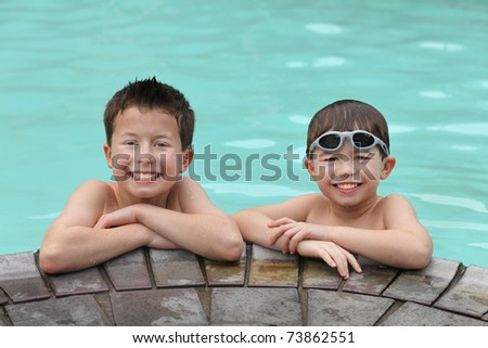 two cute young boys at the edge of a swimming pool - stock photo