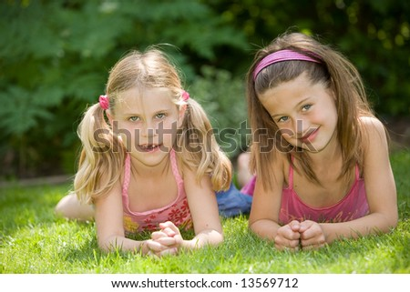 Two cute young girls lying in the grass together on a summer day - stock photo
