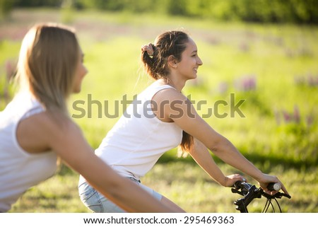 Two cute young happy smiling beautiful girlfriends wearing casual white tank tops enjoy cycling in park on sunny summer day, focus on brunette young woman profile - stock photo