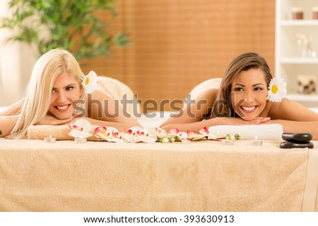 Two cute young women enjoying during a skin care treatment at a spa.  - stock photo