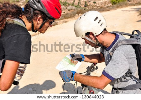 Two cyclist men read the map on the bicycle trail - stock photo