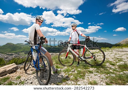 two cyclists stopped in the mountains to enjoy the view - stock photo