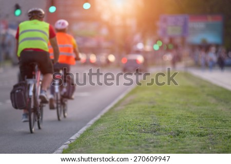 Two cyclists with protective equipment are approaching an intersection in a busy part of the city towards the setting sun. Shallow depth of field, focus on the grass in the foreground. - stock photo