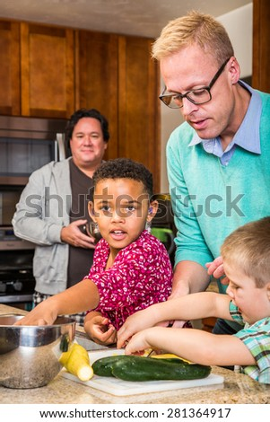 Two dads in kitchen cook with children - stock photo