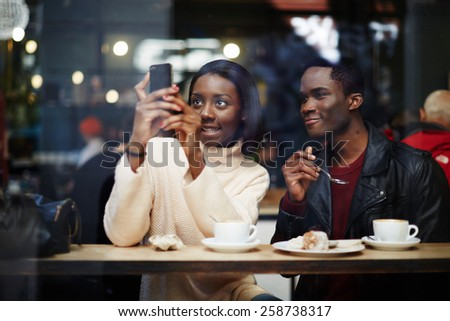 Two dark skinned stylish friends having breakfast in cafe, attractive black woman taking the picture with digital camera on smart phone sitting in beautiful coffee shop, view through cafe window - stock photo