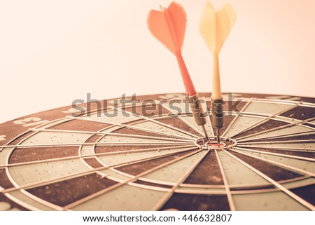 Two darts arrows in the target center. - Vintage Tone. - stock photo