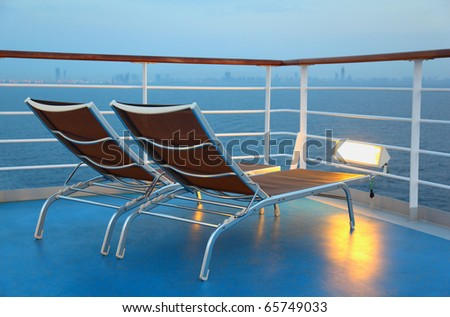 Two deck-chair are on the ship overlooking the city in the evening and illuminated by yellow light - stock photo