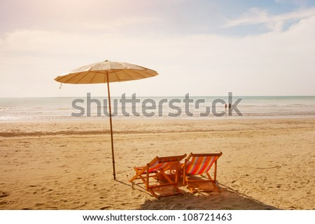two deck chairs and umbrella - stock photo