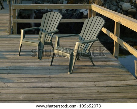 Two deck chairs on a dock at sunset - stock photo