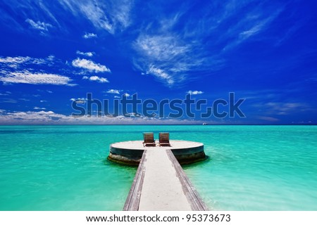 Two deck chairs on stunning empty tropical beach - stock photo