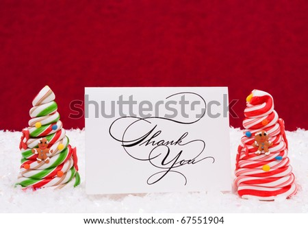 Two decorated candy cane trees on snow with a red background, thank you - stock photo