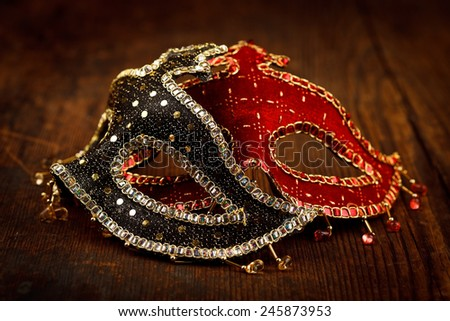 Two decorated festive masks on wooden table - stock photo
