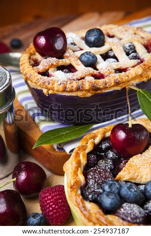Two decorated homemade shortcrust pastry berry pies with striped cloth, shiny metal icing sugar shaker, spoon and selection of berries on grunge style wooden table.   - stock photo