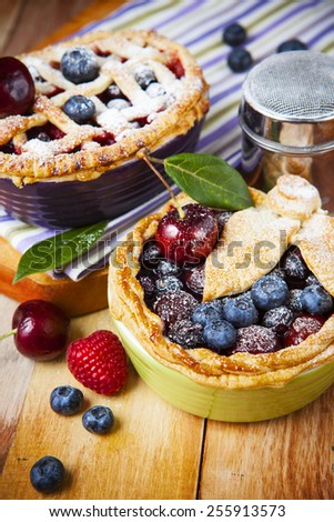 Two decorated homemade shortcrust pastry berry pies with striped cloth, shiny metal icing sugar shaker and selection of berries on grunge style wooden table.   - stock photo