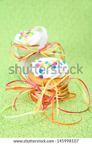 Two Decorated vanilla cupcakes on a green background - stock photo