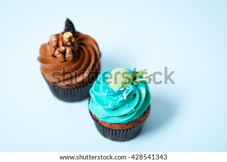 Two delicious cupcakes with cream on a blue background - stock photo