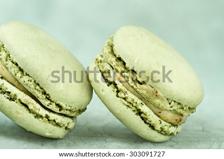Two delicious green Pistashio flavored macarons. Extreme shallow depth of field with selective focus on macarons. - stock photo