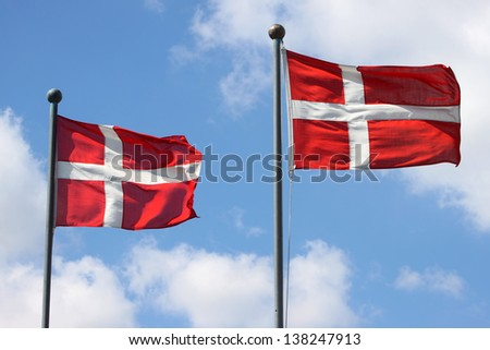 Two Denmark flags waving on wind against the blue sky with clouds - stock photo
