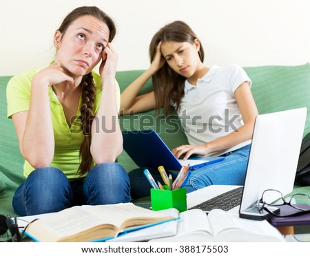 Two depressed student sitting on the couch and working on laptop computers. Focus on the left woman - stock photo