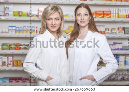 Two determined female pharmacists with coats in pharmacy environment - stock photo