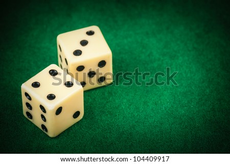 Two dice on a green gaming table with space for text - stock photo