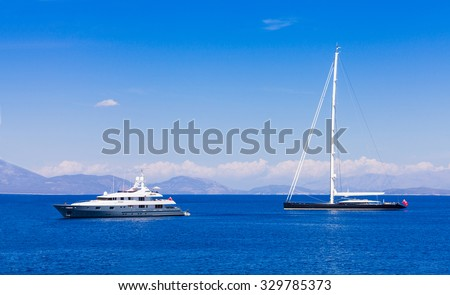 Two different types of yachts in the ocean: a motorized luxury yacht and one hybrid (sailing and motorized) cruising yacht. - stock photo