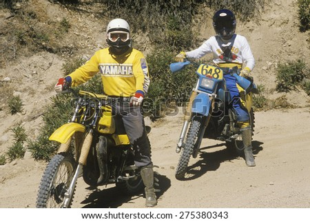 Two dirt bike riders on their off-road motorcycles - stock photo