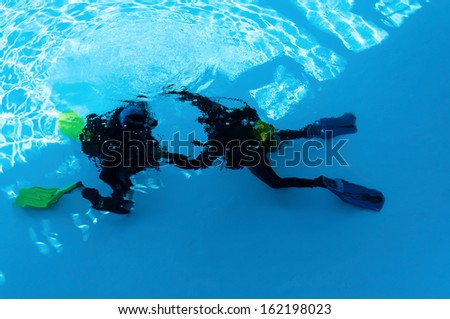 Two divers are trained in the pool - stock photo