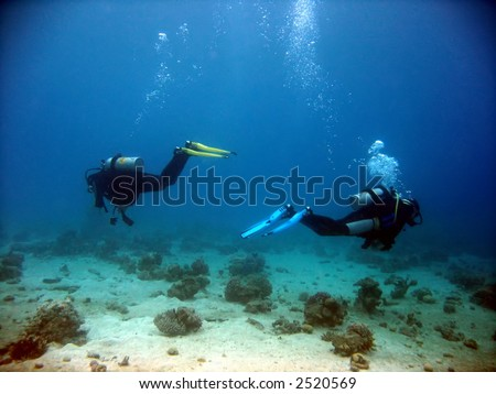 Two divers parting each other underwater - stock photo