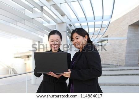 Two diverse business woman at office building with laptop computer - stock photo