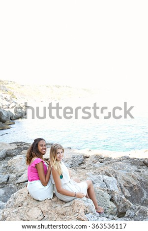 Two diverse friends, caucasian and african american teenager girls together on textured rocks smiling at camera, relaxing by the sea, outdoors. Healthy well being holiday lifestyle, beach exterior. - stock photo