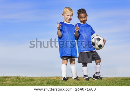 Two diverse young soccer players showing No. 1 sign. Full length view of two youth recreation league soccer players - stock photo