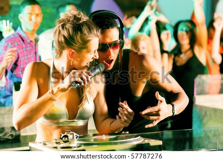 Two DJs - male and female, black and white - in a club at the turntable, in the background a crowd of their fans cheering - stock photo