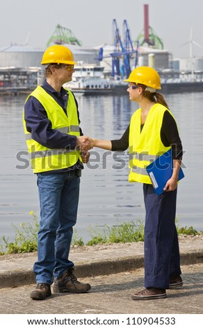 Two dockers, a man and a woman shaking hands in an industrial harbor, wearing the necessary safety gear - stock photo