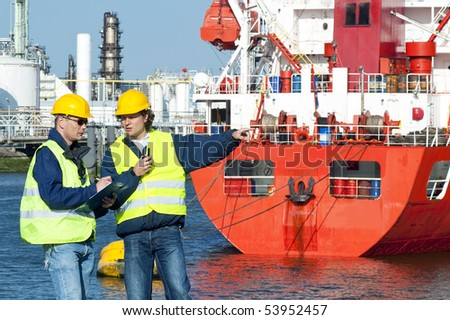 Two dockers at work, wearing safety vests hand hard hats, in frond of a red fire boat at a petrochemical harbor - stock photo