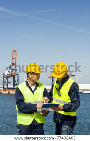Two dockers discussing procedures and plans at the waters edge - stock photo